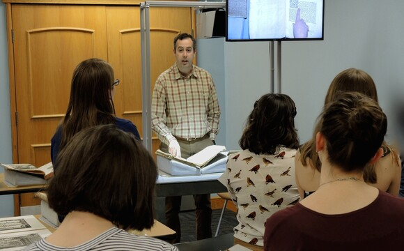 The monitor is shown mounted on the cart during a class with Dr. Robin Thomas, Associate Professor of Art History.