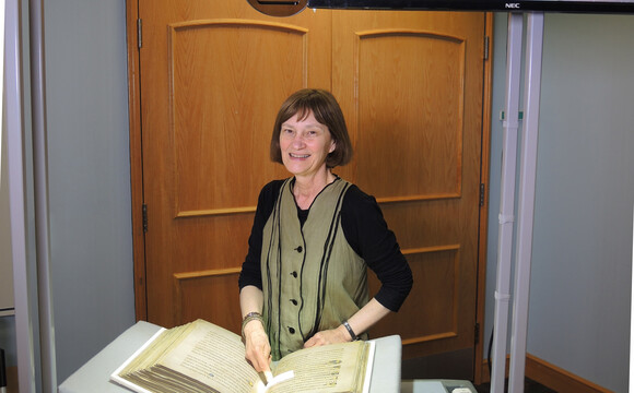 Rare Books Curator, Sandra Stelts with a facsimile of the BOOK OF KELLS and an illuminated initial letter, Spring semester 2017.