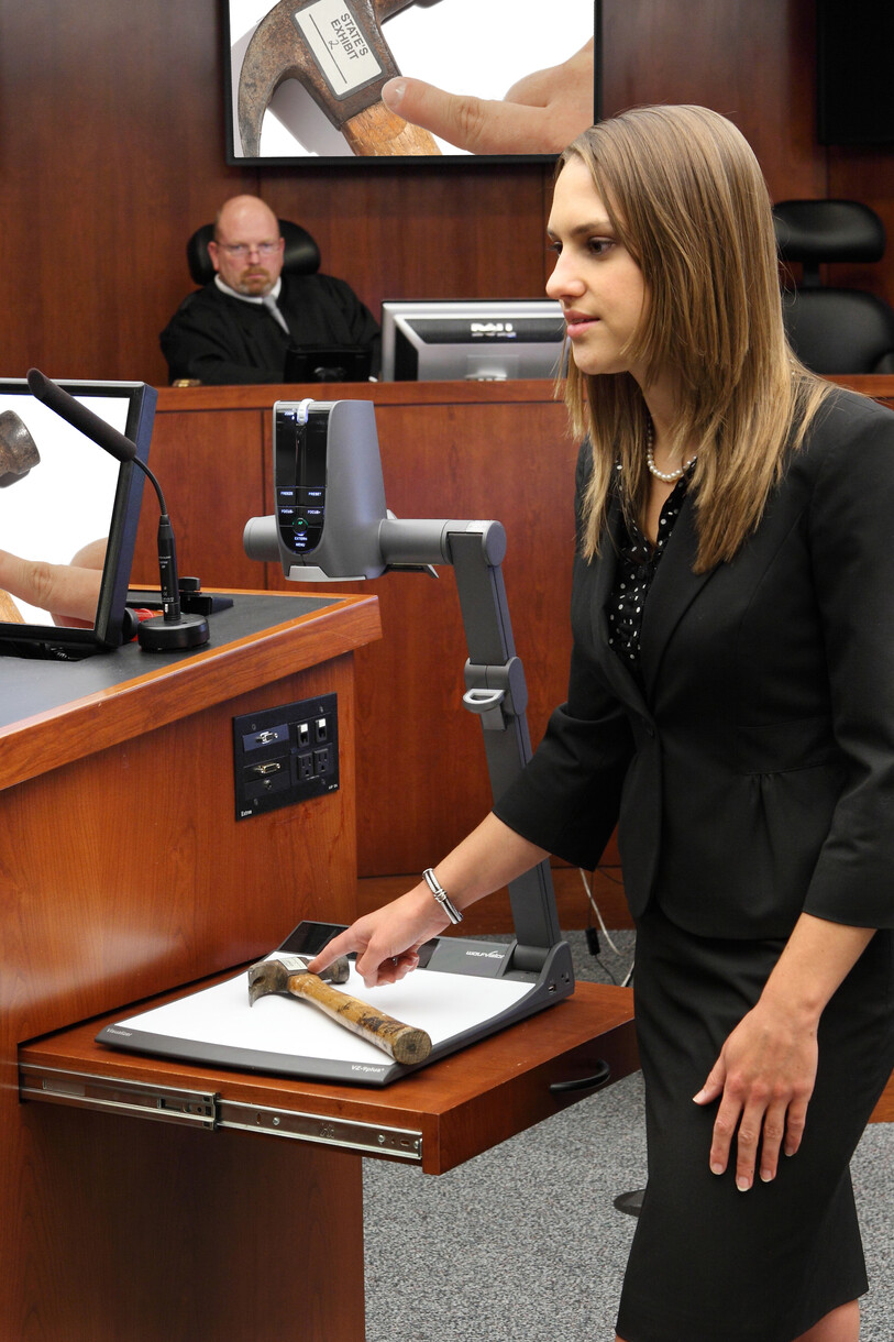 A law student using a WolfVision VZ-9plus³ to present evidence during a mock trial in the McGlothlin Courtroom.